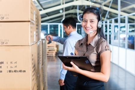 Young Asian woman in a suit with headset in a indonesian warehouse, she is from the Customer Service, a coworker standing in background photo