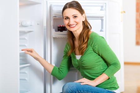 fridge: Young woman or housekeeper defrosts the refrigerator and wipes in clean