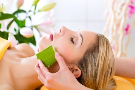 reiki: Wellness - woman receiving head or face massage whit aloe Vera in spa Stock Photo