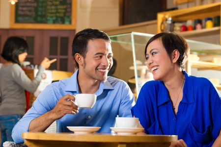 Asian friends enjoying her leisure time in a cafe, drinking coffee or cappuccino and talking about some things photo