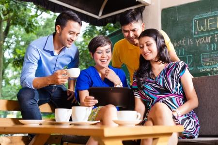 group picture: Amigos asi�ticos o compa�eros de trabajo disfrutar del tiempo libre en un caf�, beber caf� o capuchino y mirar fotos o mensajes de correo electr�nico en un equipo Tablet PC