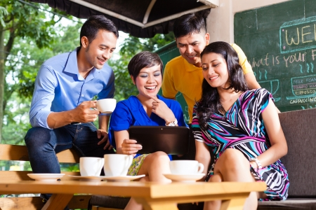 Asian friends or colleagues enjoying leisure time in a cafe, drinking coffee or cappuccino and looking at photos or emails on a tablet computer