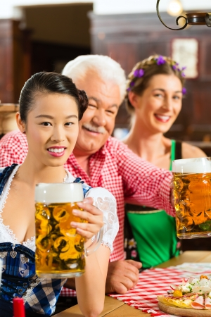 In Pub - friends in Tracht, Dirndl and Lederhosen drinking a fresh beer in Bavaria, Germany Stock Photo - 23511565