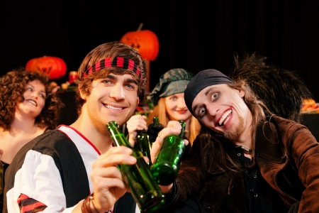 funny costume: Group of young people celebrating a carnival or Halloween party in costumes drinking beer