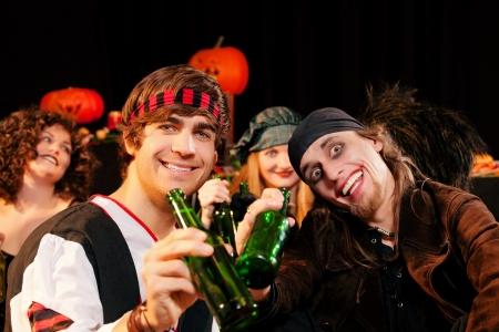 personas festejando: Grupo de j�venes celebran una fiesta de carnaval o Halloween con disfraces beber cerveza Foto de archivo