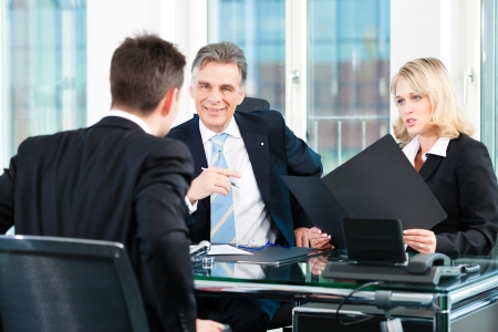 applicant: Business - young man sitting in job Interview Stock Photo
