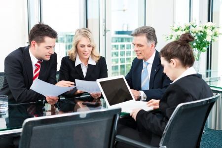 discuss: Business - meeting in an office, the businesspeople are discussing a document