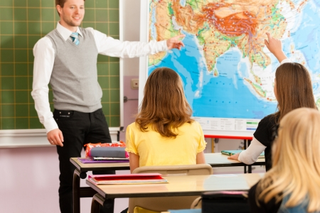 Education - Young teacher with pupil in his form of the elementary or primary school teaching Stock Photo