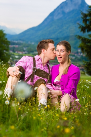 Happy Couple in traditional dress sitting in the meadow with mountain panorama photo