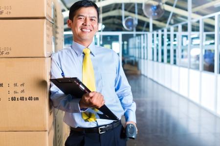 supervisores: Hombre indonesio joven en un traje con un esc�ner de c�digo de barras en un almac�n asi�tico de la expedici�n o la empresa de log�stica Foto de archivo