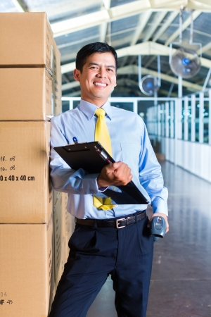 convinced: Young Indonesian man in a suit with a bar code scanner in a Asian warehouse of forwarding or logistics company