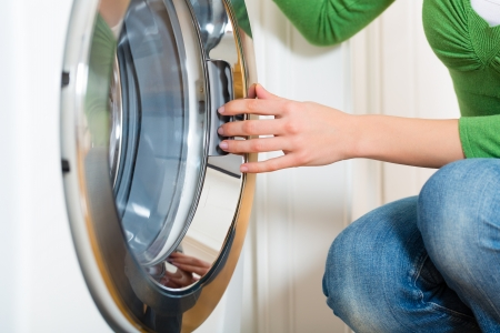 home appliance: Young woman or housekeeper has a laundry day at home, she takes the laundry or whites out of your washing machine or the dryer