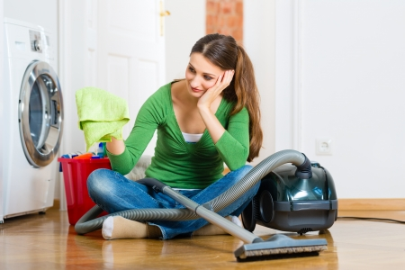 apartment cleaning: Young woman cleaning at home, she has a cleaning day and using a vacuum cleaner cleaning products and a bucket but she does not feel like it
