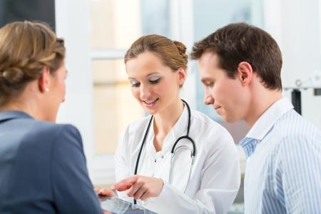 pacientes: Mujeres médico con sus pacientes en la clínica explicando algo