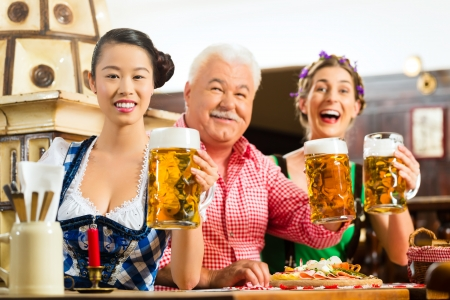 In Pub - friends in Tracht, Dirndl and Lederhosen drinking a fresh beer in Bavaria, Germany Stock Photo - 23512161