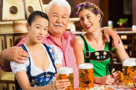 lederhosen: In Pub - friends in Tracht, Dirndl and Lederhosen drinking a fresh beer in Bavaria, Germany Stock Photo