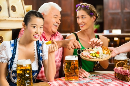 In Pub - friends in Tracht, Dirndl and Lederhosen drinking a fresh beer in Bavaria, Germany Stock Photo - 23512163
