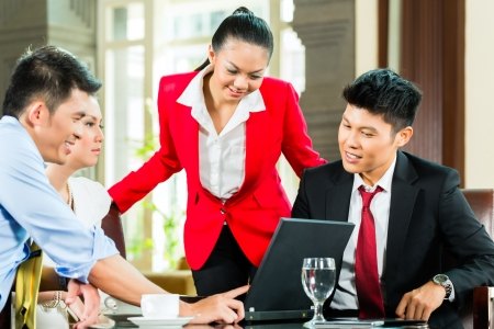 Four Chinese Asian business men and women having meeting in a hotel lobby looking at documents on laptop and drinking coffee photo