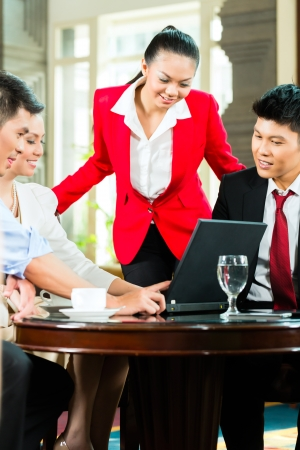 Four Chinese Asian business men and women having meeting in a hotel lobby looking at documents on laptop and drinking coffee Stock Photo - 23512166