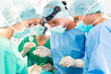 Hospital - surgery team in the operating room or Op of a clinic operating on a patient, perhaps its an emergency