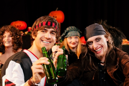 halloween costume: Group of young people celebrating a carnival or Halloween party in costumes drinking beer