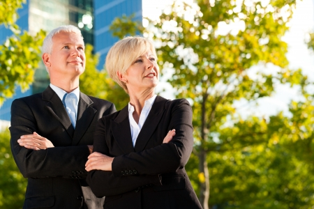 front office: Business people - mature or senior - standing in a park outdoors in front of a office building Stock Photo