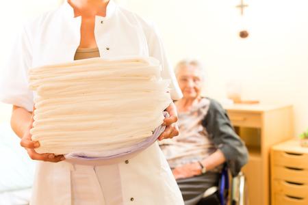 Jonge verpleegster en vrouwelijke oudste in verpleeghuis, de handdoeken zal worden veranderd Stockfoto