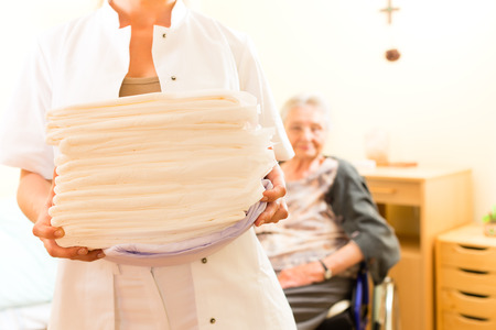 diaper changing: Young nurse and female senior in nursing home, the towels going to be changed