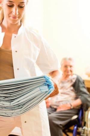Laundry: Enfermera de los j�venes y de sexo femenino mayor en el hogar de ancianos, las toallas va a ser cambiado Foto de archivo