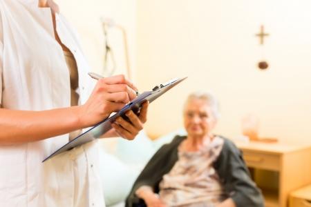 Jonge verpleegster en vrouwelijke oudste in verpleeghuis worden metingen genomen of administratieve taken verzorgd
