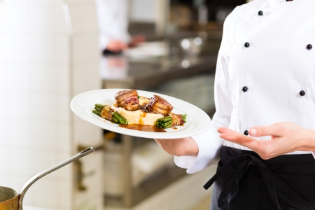 Female Chef in hotel or restaurant kitchen cooking, only hands to be seen, she is presenting a dish Stock Photo - 23760023
