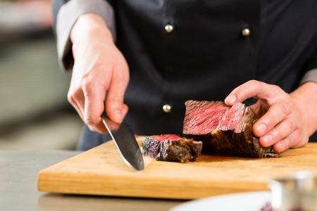 meat dish: Chef in hotel or restaurant kitchen cooking, only hands, he is cutting meat or steak