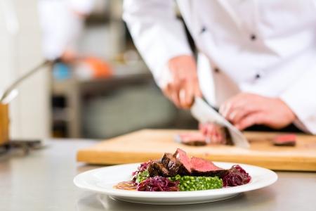 резка: Шеф-повар в отеле или ресторане приготовления пищи на кухне, только руки, он режет мясо или стейк на блюдо на тарелке