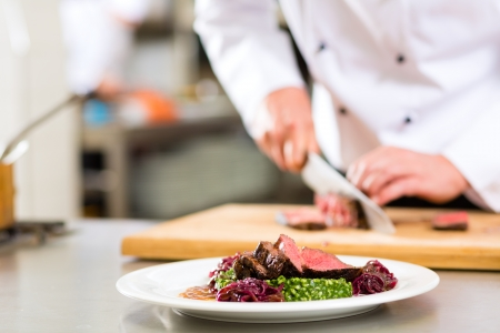 cooking chef: Chef in hotel or restaurant kitchen cooking, only hands, he is cutting meat or steak for a dish on plate