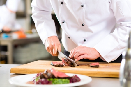steak plate: Chef in hotel or restaurant kitchen cooking, only hands, he is cutting meat or steak for a dish on plate