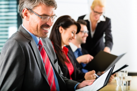 know how: Business - businesspeople have a meeting with presentation in office, they negotiate a contract - Portrait of a businessman