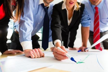Empresas - Cuatro profesionales de la oficina en ropa de trabajo en la planificación de una estrategia para el futuro de la empresa