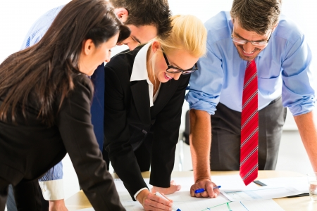 professional occupations: Business - Four professionals in the office in business clothes when planning a strategy for the future of the business