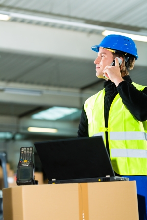 warehouseman: Warehouseman with protective vest, scanner and laptop in warehouse at freight forwarding company using a mobile phone Stock Photo