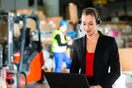 forwarding: Friendly Woman, dispatcher or supervisor using headset and laptop at warehouse of forwarding company, smiling, a forklift is in Background