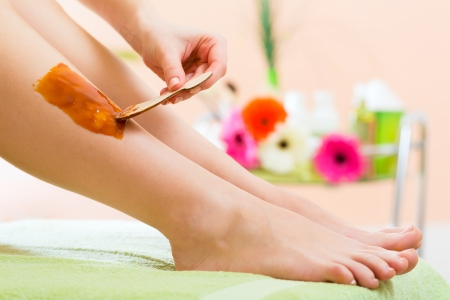 waxing: Young woman in Spa getting legs waxed for hair removal
