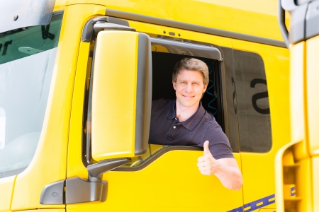 truck driver: Logistics - proud driver or forwarder in drivers cap of truck and trailer, on a transshipment point
