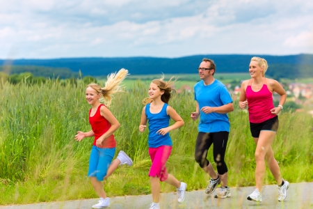 Family - mother, father and four children - doing jogging or outdoor sport for fitness on rural street photo