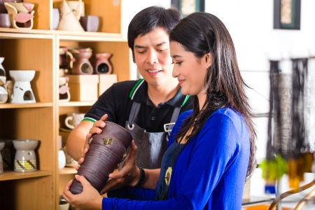 speaks: Asian seller or souvenir dealer speaks with an Indonesian customer at a shop and shows her pottery