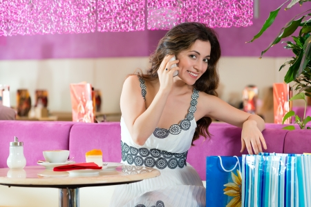 Young woman in a cafe or ice cream parlor eating a cake and using her phone, maybe she is single or waiting for someone photo