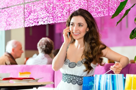 Young woman in a cafe or ice cream parlor eating a cake and using her phone, maybe she is single or waiting for someone Stock Photo - 23760459