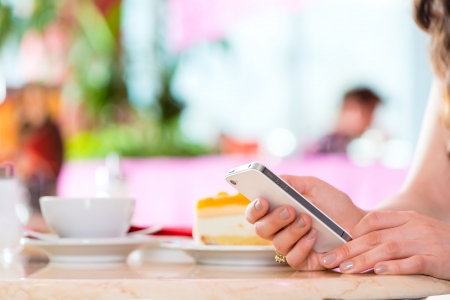 Young woman in a cafe or ice cream parlor using her phone, maybe she is single or waiting for someone photo