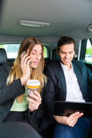 Young businesspeople with mobile phone and tablet computer traveling in taxi, they are colleagues photo