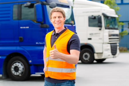 truck driver: Logistics - proud driver or forwarder in front of trucks and trailers, on a transshipment point