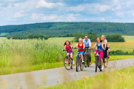 美しい風景の中の夏の日に彼らのバイクに週末の遠足を持つ 3 人の女の子と家族